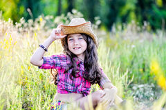 Little girl sitting in a field wearing a cowboy hat Royalty Free Stock Images