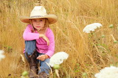 Little girl sitting in a field wearing large hat. A cute little 6 year old girl with blond hair wearing a cowboy hat sitting in tall grass and white wild Royalty Free Stock Photography