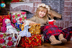 The little girl  is sitting at a fireplace and Christmas gifts. Royalty Free Stock Image