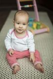 Little girl sitting on the floor on the carpet royalty free stock photo