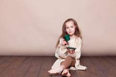 Little girl sitting on the floor and drinking tea royalty free stock images