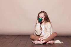 Little girl sitting on the floor and drinking tea royalty free stock photos