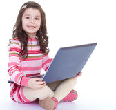 Little girl sitting on the floor with a laptop. Stock Image