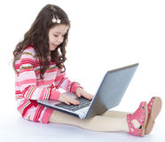 Little girl sitting on the floor with a laptop. Stock Images