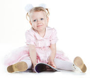 Little girl sitting on the floor with magazine. Isolated on white Royalty Free Stock Photo