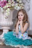 A little girl is sitting on the floor near a big vase with flowers. Stock Image