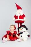 Little girl sitting on the floor near christmas toys Stock Photography