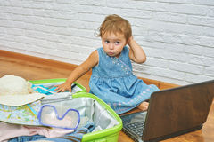 Little girl sitting on the floor near the suitcase and laptop .to prepare for the trip . Royalty Free Stock Image