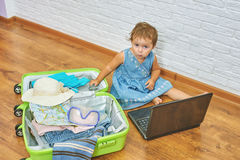 Little girl sitting on the floor near the suitcase and laptop .to prepare for the trip . Stock Photo