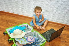 Little girl sitting on the floor near the suitcase and laptop .to prepare for the trip . Stock Images