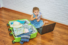 Little girl sitting on the floor near the suitcase and laptop .to prepare for the trip . Royalty Free Stock Photography