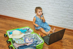 Little girl sitting on the floor near the suitcase and laptop .to prepare for the trip . Royalty Free Stock Photo