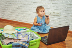 Little girl sitting on the floor near the suitcase and laptop .to prepare for the trip . Royalty Free Stock Images