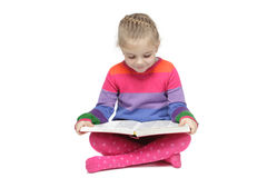 Little girl sitting on the floor reading the book Royalty Free Stock Photos