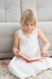 Little girl sitting on the floor reading storybook Stock Photography