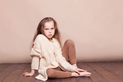 Little girl sitting on the floor and sad stock photo