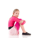 Little girl sitting on the floor, Side view. Royalty Free Stock Photo