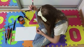 Little Girl start drawing. Little Girl sitting on floor and start drawing top view stock footage