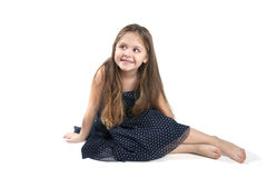 Little girl sitting on the floor. Studio photography on a pure white background royalty free stock photography
