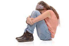 Little girl sitting on the floor and sulking, white background Royalty Free Stock Image