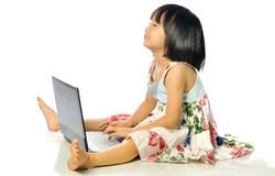 Little girl sitting on floor using a laptop, white background Stock Photos