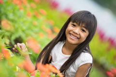 Little girl sitting on flower field Stock Photos