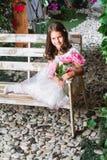 Little girl sitting in the flowered garden Stock Photography
