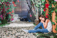 Little girl sitting in the flowered garden Royalty Free Stock Images