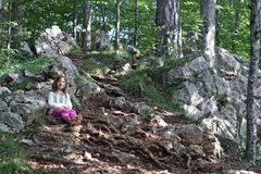 Little girl sitting in forest Stock Photography