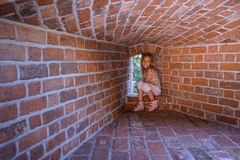 Little girl sitting on the fortress wall Royalty Free Stock Images