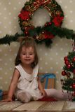 Little girl sitting in front of a Christmas tree Royalty Free Stock Photo