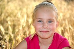 Little girl sitting  in  gold grass on a summer. Little girl sitting  in a big gold grass on a summer meadow .Summer background Stock Photos