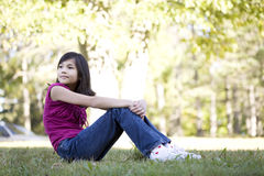 Little girl sitting on grass Stock Photography