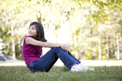 Little girl sitting on grass royalty free stock images