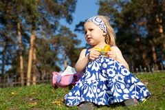 Little girl is sitting on grass Royalty Free Stock Image