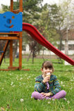Little girl sitting on grass and eat ice cream Stock Image