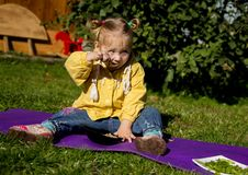 Little girl is sitting on a grass and eating porridge royalty free stock photo