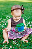Little girl sitting on the grass and eats candy Stock Image