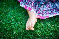 Little girl sitting on the grass Stock Images