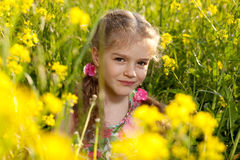 Little girl sitting in the grass and flowers Royalty Free Stock Photos