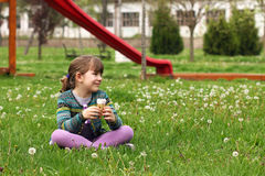 Little girl sitting on grass with ice cream Stock Image