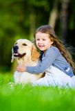 Little girl sitting on the grass with labrador Stock Photography