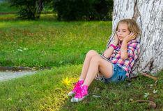 Little girl sitting on grass near a tree and listening to the mu Stock Images