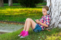 Little girl sitting on grass near a tree and listening to the mu Royalty Free Stock Photos