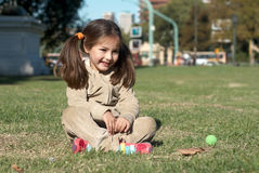 The little girl sitting on a grass in park Royalty Free Stock Photography