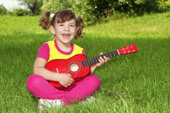 Little girl sitting on grass play guitar Royalty Free Stock Photography