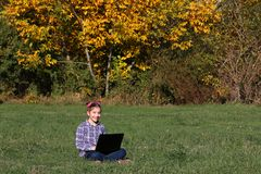 Little girl sitting on grass and playing laptop Royalty Free Stock Photo