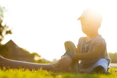 Little girl sitting on the grass and putting flip flips on mothe Royalty Free Stock Images