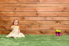 Little girl sitting on the grass. Showing on something, there are a number of rubber boots on background wooden wall stock photos
