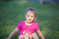 Little girl sitting on the grass in sunlight. Little girl in pink tshirt sitting on the grass in the sunlight Stock Images